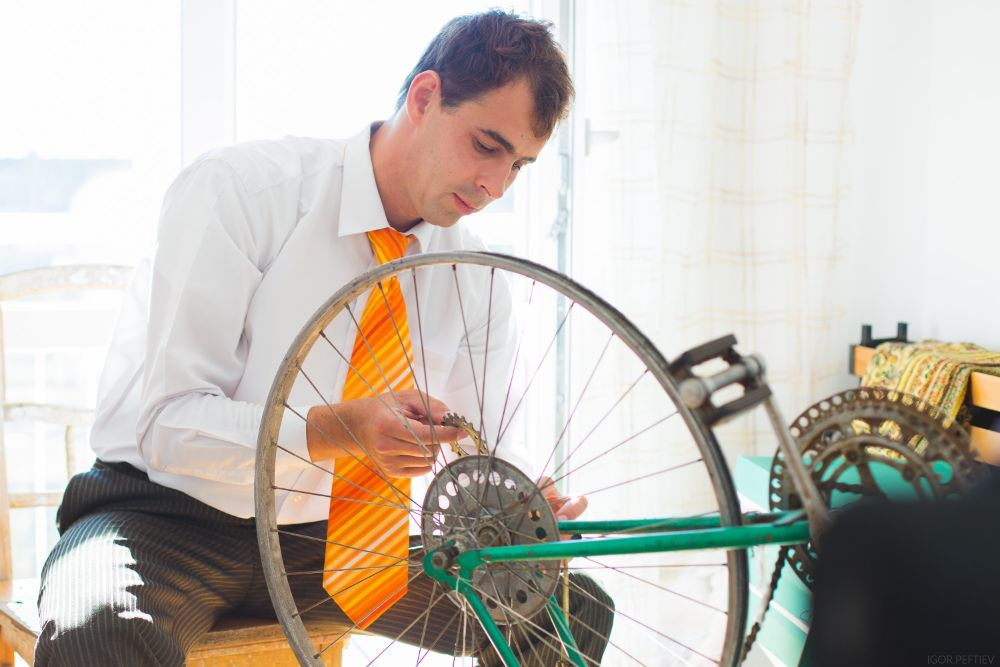 Man in suit fixing bicycle