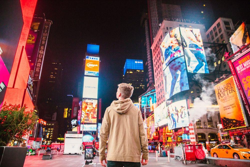 Man looking at street advertisements